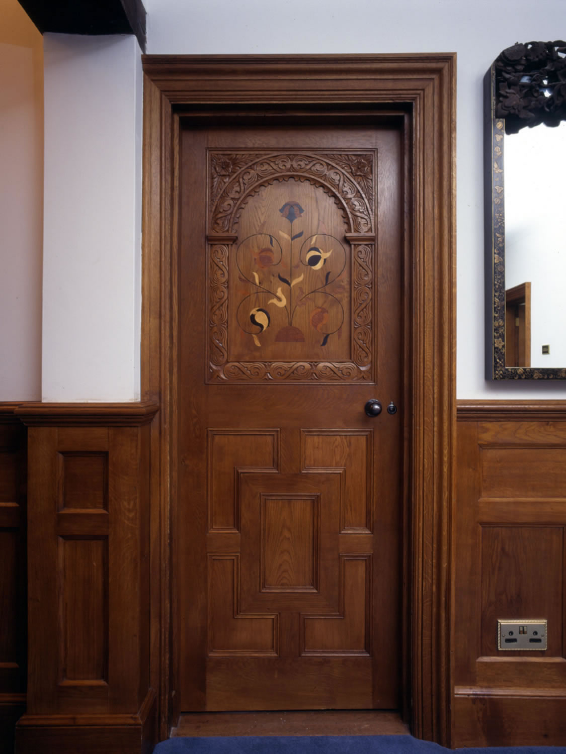 C17th style oak panelled door with carved arcade and inlaid decoration