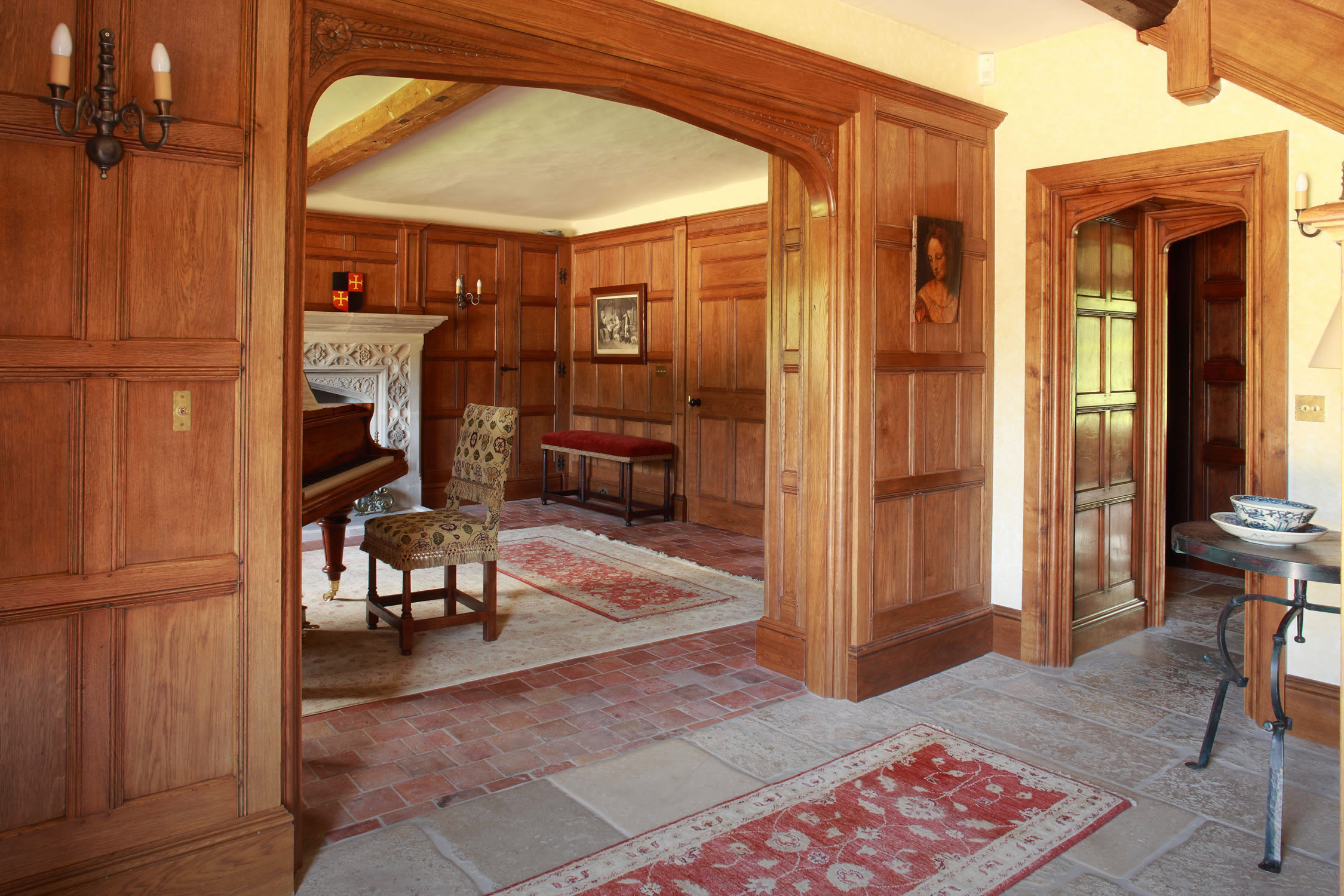 Oak panelled entrance hall with Tudor arched opening